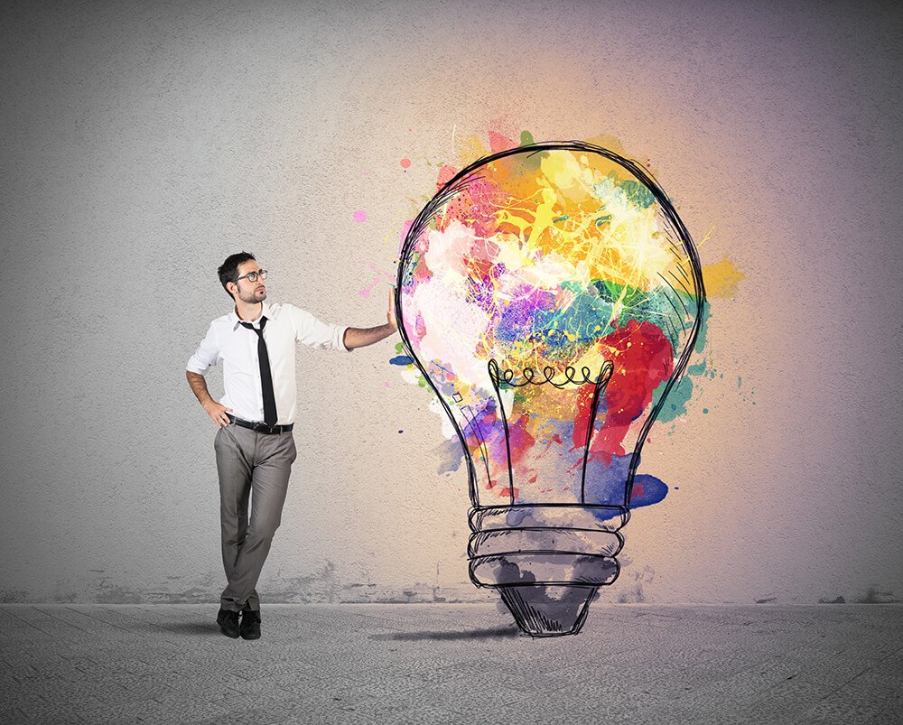 image shows a metaphor for creative thinking, man in a shirt and tie leaning against a colourful lighbulb