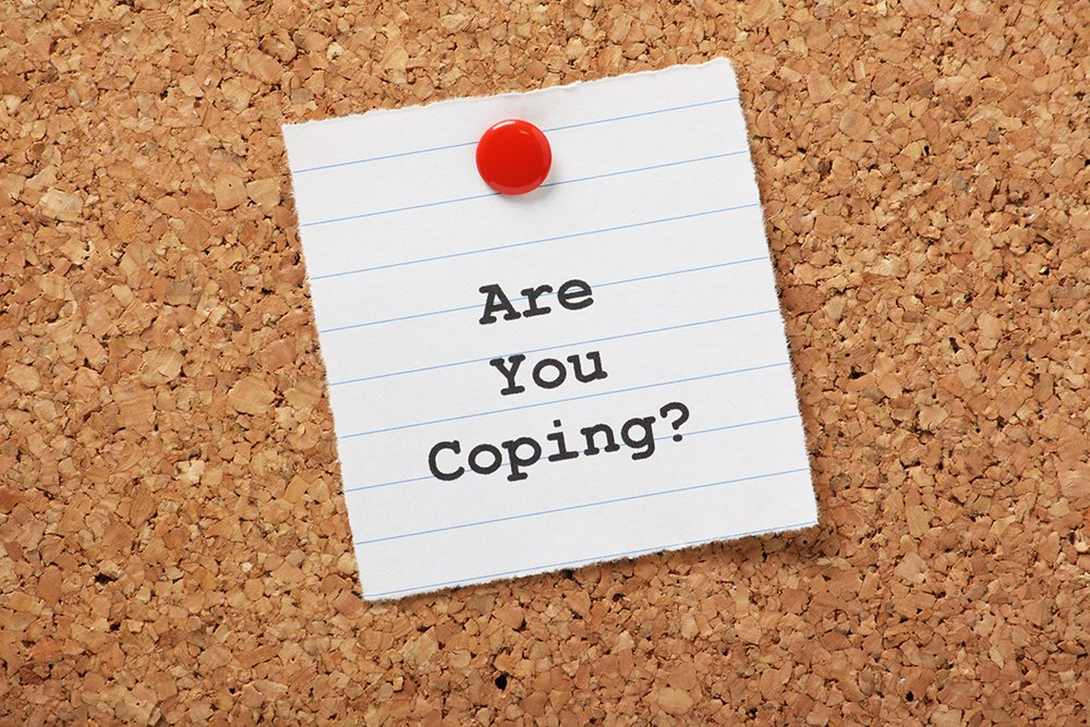 image shows a piece of paper tacked to a corkboard in the workplace, the paper reads 'are you coping?'