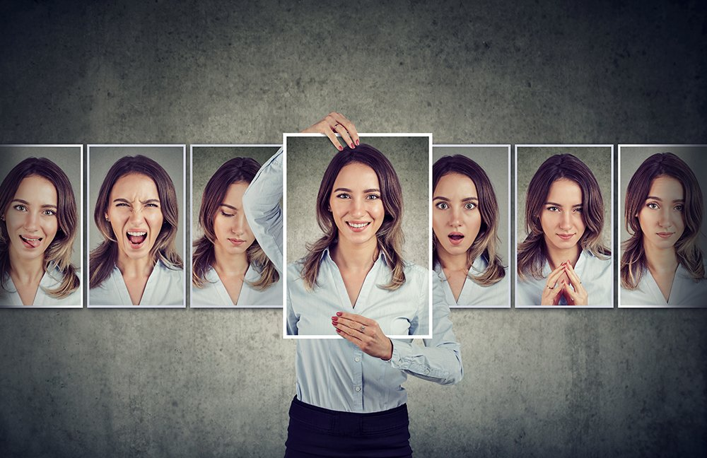 image shows a woman holding up photos of a range of different emotions and mindsets